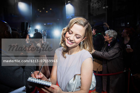 Well dressed female celebrity signing autographs at red carpet event Stock Photo - Premium Royalty-Free, Image code: 6113-07159963
