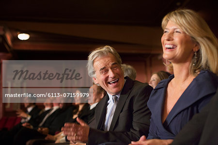 Couple laughing and clapping in theater Stock Photo - Premium Royalty-Free, Image code: 6113-07159979