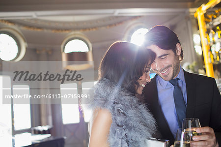 Well dressed couple drinking champagne in luxury bar Stock Photo - Premium Royalty-Free, Image code: 6113-07159991