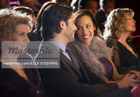 Smiling couple talking in theater audience Stock Photo - Premium Royalty-Free, Image code: 6113-07159995