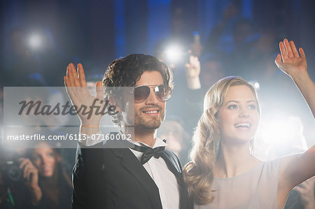 Well dressed celebrity couple waving to paparazzi Stock Photo - Premium Royalty-Free, Image code: 6113-07160002