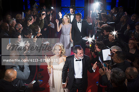 Well dressed celebrities waving to paparazzi on red carpet Stock Photo - Premium Royalty-Free, Image code: 6113-07160023