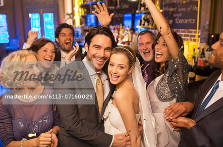 Friends cheering around smiling bride and groom at wedding reception Stock Photo - Premium Royalty-Free, Image code: 6113-07160029