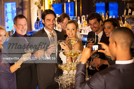 Man photographing bride and groom with friends at champagne pyramid Stock Photo - Premium Royalty-Free, Image code: 6113-07160036