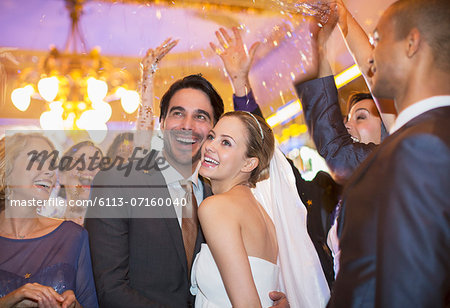 Friends throwing confetti over bride and groom at wedding reception Stock Photo - Premium Royalty-Free, Image code: 6113-07160040