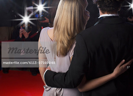 Close up rear view of celebrity couple hugging for paparazzi on red carpet Stock Photo - Premium Royalty-Free, Image code: 6113-07160048