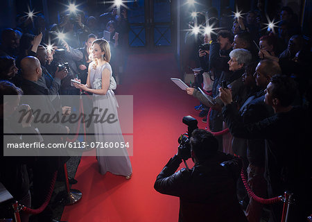 Well dressed female celebrity signing autographs and posing for paparazzi on red carpet Stock Photo - Premium Royalty-Free, Image code: 6113-07160054