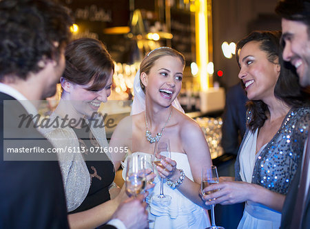 Happy bride drinking champagne with friends at wedding reception Stock Photo - Premium Royalty-Free, Image code: 6113-07160055