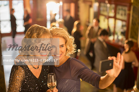 Well dressed women with champagne taking self-portrait with camera phone in theater lobby Stock Photo - Premium Royalty-Free, Image code: 6113-07160057
