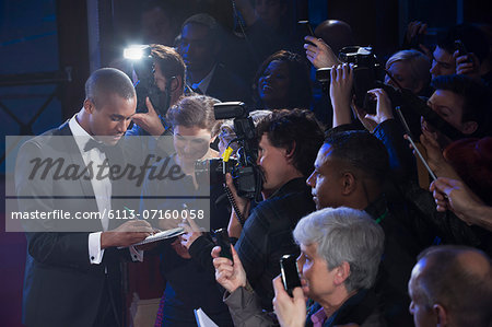 Well dressed male celebrity signing autographs at red carpet event Stock Photo - Premium Royalty-Free, Image code: 6113-07160058