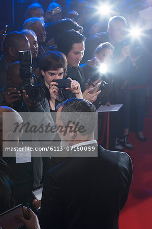 Well dressed male celebrity signing autographs at red carpet event Stock Photo - Premium Royalty-Free, Image code: 6113-07160059