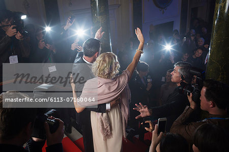 Rear view of well dressed celebrity couple waving to paparazzi on red carpet Stock Photo - Premium Royalty-Free, Image code: 6113-07160064