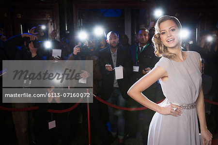 Portrait of well dressed female celebrity at red carpet event with paparazzi in background Stock Photo - Premium Royalty-Free, Image code: 6113-07160072