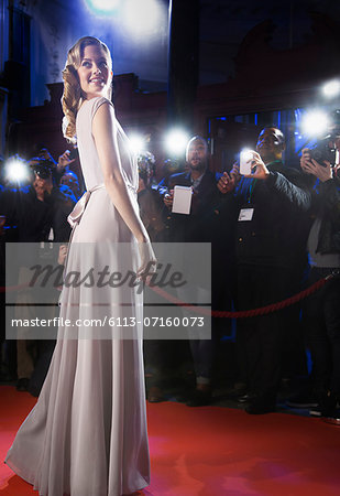Well dressed female celebrity posing for paparazzi on red carpet Stock Photo - Premium Royalty-Free, Image code: 6113-07160073