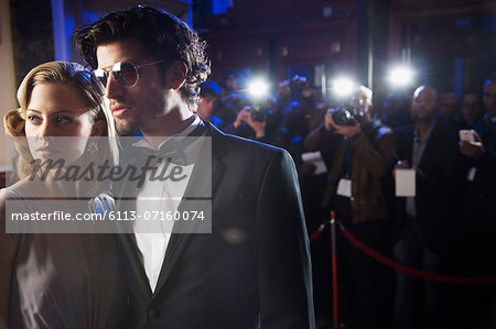 Close up of well dressed celebrity at red carpet event with paparazzi in background Stock Photo - Premium Royalty-Free, Image code: 6113-07160074