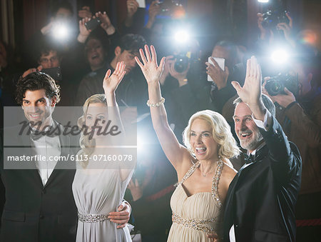 Well dressed celebrity couples waving to paparazzi at red carpet event Stock Photo - Premium Royalty-Free, Image code: 6113-07160078
