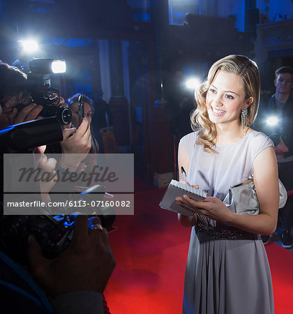 Well dressed female celebrity signing autograph and posing for paparazzi on red carpet Stock Photo - Premium Royalty-Free, Image code: 6113-07160082