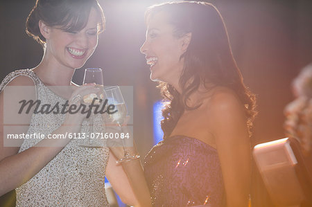 Well dressed women toasting champagne flutes Stock Photo - Premium Royalty-Free, Image code: 6113-07160084
