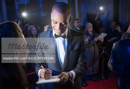 Well dressed celebrity signing autograph on red carpet Stock Photo - Premium Royalty-Free, Image code: 6113-07160085