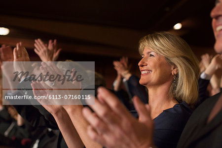 Close up of enthusiastic woman clapping in theater audience Stock Photo - Premium Royalty-Free, Image code: 6113-07160115