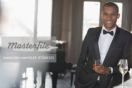 Portrait of well dressed man drinking cocktail in lounge Stock Photo - Premium Royalty-Free, Image code: 6113-07160121
