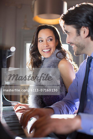 Close up of well dressed couple playing piano in lounge Stock Photo - Premium Royalty-Free, Image code: 6113-07160130