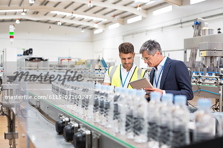 Supervisor and manager watching plastic bottles on conveyor belt Stock Photo - Premium Royalty-Free, Image code: 6113-07160247