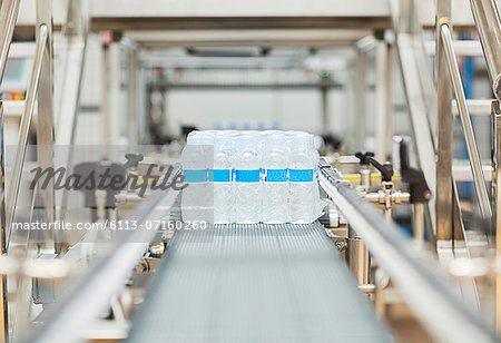 Water bottles on conveyor belt in factory Stock Photo - Premium Royalty-Free, Image code: 6113-07160260