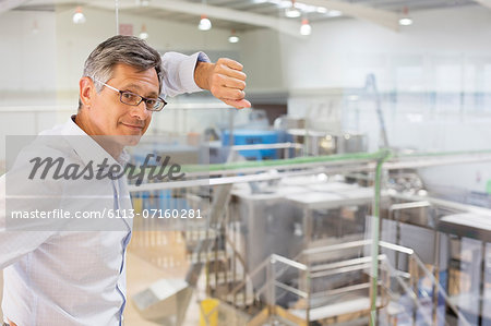 Businessman leaning on window overlooking factory Stock Photo - Premium Royalty-Free, Image code: 6113-07160281