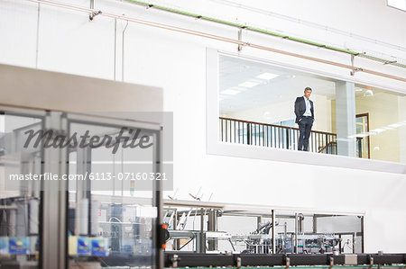 Businessman in window overlooking factory Stock Photo - Premium Royalty-Free, Image code: 6113-07160321