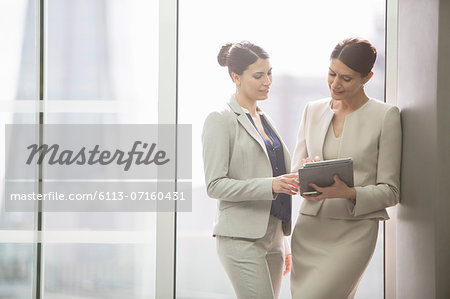 Businesswomen using digital tablet in office Stock Photo - Premium Royalty-Free, Image code: 6113-07160431