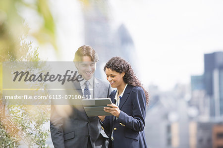 Business people using digital tablet outdoors Stock Photo - Premium Royalty-Free, Image code: 6113-07160451