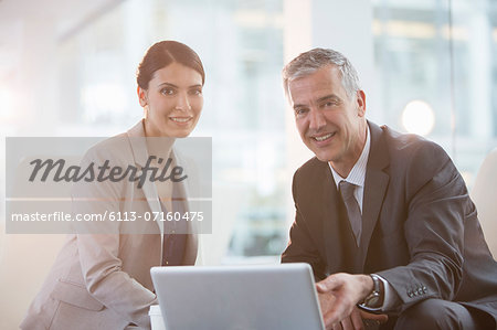 Business people using laptop in office Stock Photo - Premium Royalty-Free, Image code: 6113-07160475