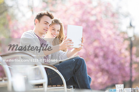Couple using digital tablet in park Stock Photo - Premium Royalty-Free, Image code: 6113-07160605
