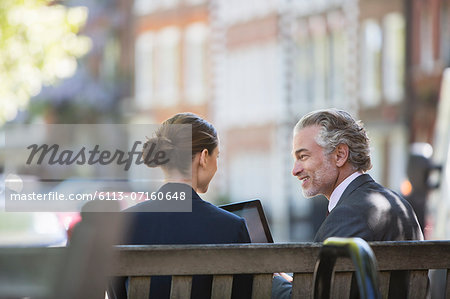 Business people talking on urban bench Stock Photo - Premium Royalty-Free, Image code: 6113-07160648