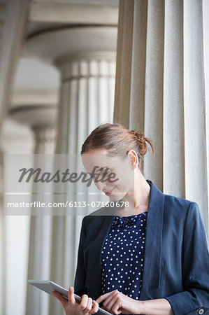 Businesswoman using digital tablet outdoors Stock Photo - Premium Royalty-Free, Image code: 6113-07160678
