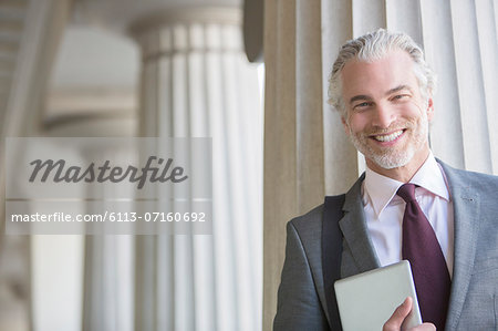 Businessman smiling outdoors Stock Photo - Premium Royalty-Free, Image code: 6113-07160692