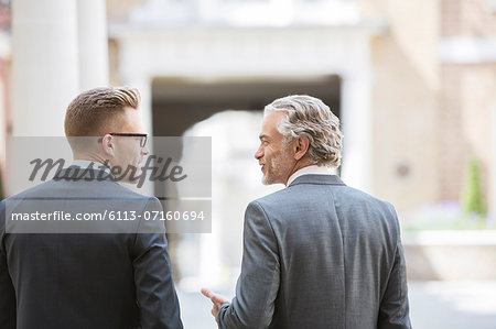 Businessmen talking on city street Stock Photo - Premium Royalty-Free, Image code: 6113-07160694