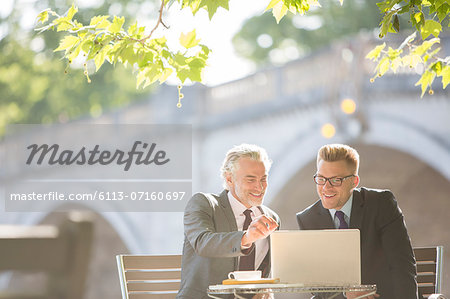 Businessmen working at sidewalk cafe Stock Photo - Premium Royalty-Free, Image code: 6113-07160697