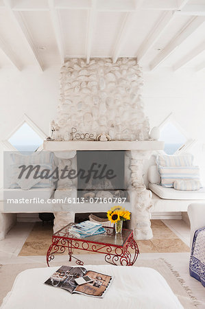 Coffee table and fireplace in white living room Stock Photo - Premium Royalty-Free, Image code: 6113-07160787