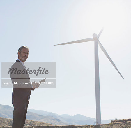 Businessman admiring wind turbine in rural landscape Stock Photo - Premium Royalty-Free, Image code: 6113-07160881