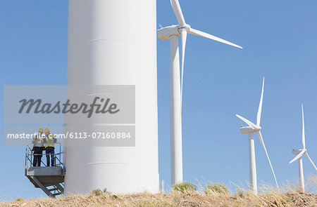 Workers talking on wind turbine in rural landscape Stock Photo - Premium Royalty-Free, Image code: 6113-07160884