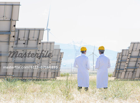 Scientists standing by solar panels in rural landscape Stock Photo - Premium Royalty-Free, Image code: 6113-07160895