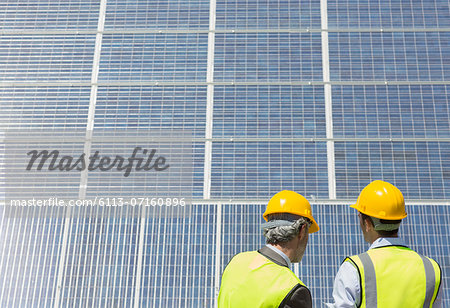 Workers examining solar panels in rural landscape Stock Photo - Premium Royalty-Free, Image code: 6113-07160896