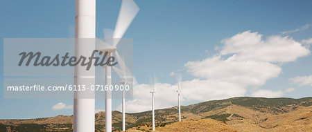 Wind turbines spinning in rural landscape Stock Photo - Premium Royalty-Free, Image code: 6113-07160900