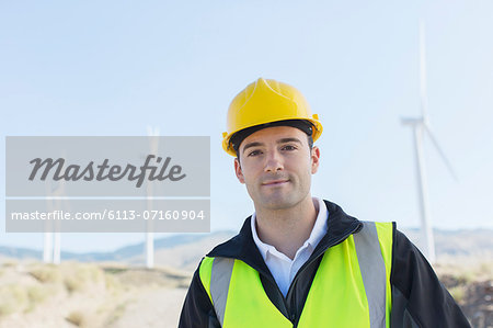 Worker standing by wind turbines in rural landscape Stock Photo - Premium Royalty-Free, Image code: 6113-07160904