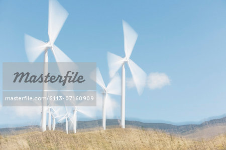 Wind turbines spinning in rural landscape Stock Photo - Premium Royalty-Free, Image code: 6113-07160909