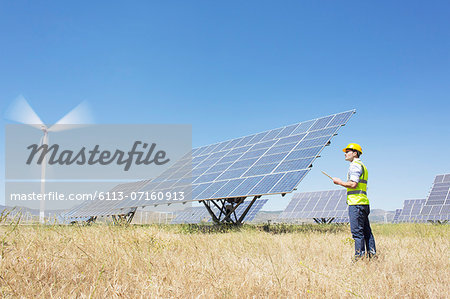Worker examining solar panels in rural landscape Stock Photo - Premium Royalty-Free, Image code: 6113-07160913