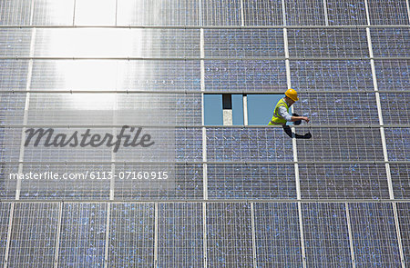 Worker examining solar panel in rural landscape Stock Photo - Premium Royalty-Free, Image code: 6113-07160915