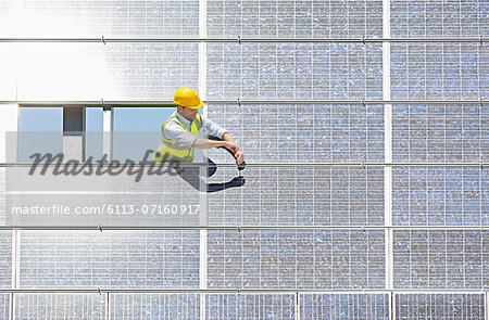 Worker examining solar panel in rural landscape Stock Photo - Premium Royalty-Free, Image code: 6113-07160917